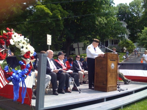 Bill Vornkahl (podium) leads his 39th Memorial Day ceremony. From left are First Selectman Gordon Joseloff, and grand marshal Ed See.