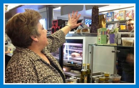 Stacey Yiozanakos waves to one of her many customers/friends, from behind the counter.