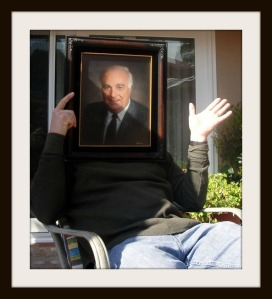 Ken Brummel, playfully hiding behind a portrait of himself.