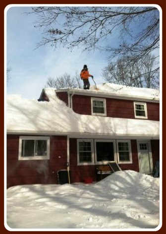 Adrian Mueller and his 9-year-old son Jaden (hidden, left) shoveled snow off their roof.
