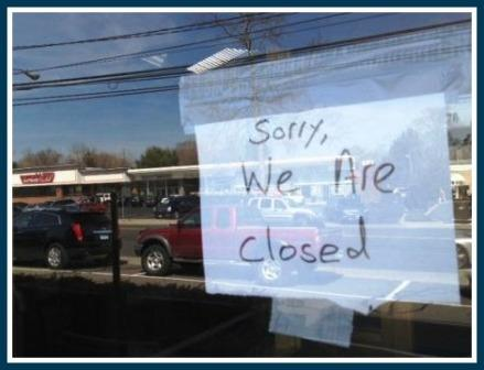 Compo Shopping Center -- across the Post Road -- is reflected in the glass door of Oaxaca. A simple sign announces the restaurant has closed.