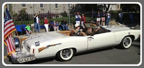 A vintage car with vintage firearms carried veterans.
