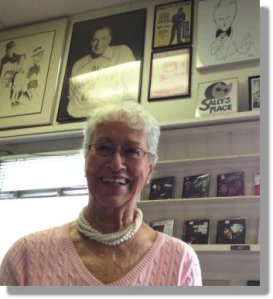 Sally White, standing underneath a photo of one of her all-time favorites: Frank Sinatra.