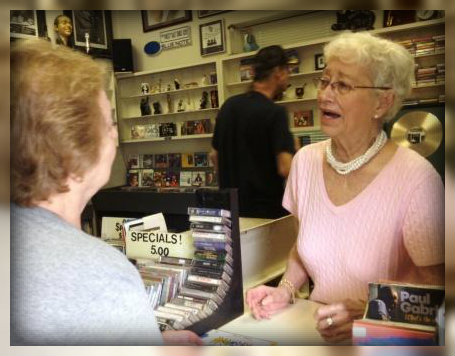 Sally doing what she loves most: interacting with one customer. Another one browses in back.