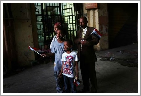 A family holds Egyptian flags on the edge of Tahrir Square.