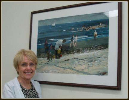 Pat Scully with Hardie Gramatky's painting of families at Compo Beach. It's hung above her desk for 20 years.