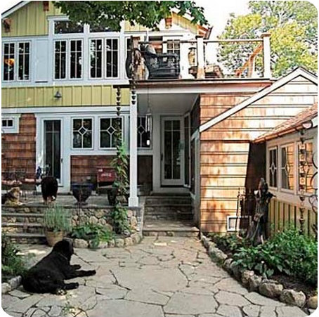 The back yard features stone paving, plants and a 2nd-store balcony.