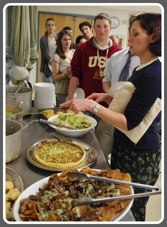 Cecily Gans and her culinary students prepare to enjoy one of their own meals. (Photo/Ben Reiser for Inklings)