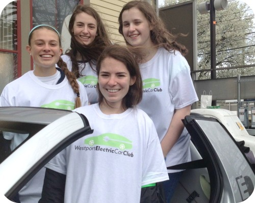 Members of Staples High School's Electric Car Club pile into a small, environmentally friendly vehicle.