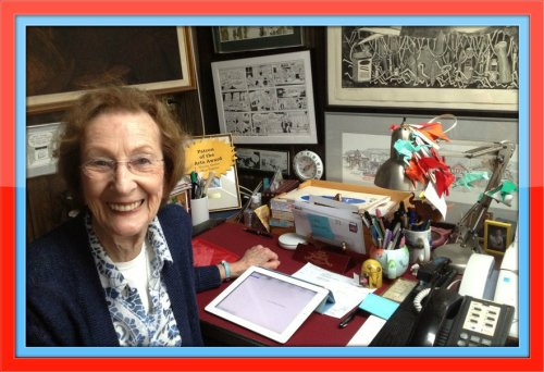 Shirley Mellor at her desk, surrounded by original art from grateful customers.