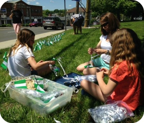 Elizabeth Baldwin, and daughters Lindsey and Abbey, place ribbons on each flag before they are placed in the ground by Matt Baldwin (background) and other volunteers.