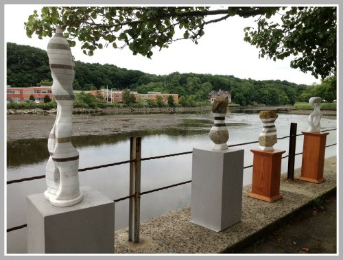 Art show culptures frame the Saugatuck River.