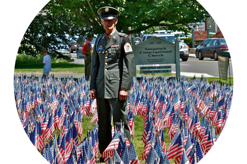 Bob Custer, standing amidst the flags he loves.