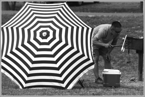 """""""Man Barbecuing Next to Black and White Umbrella"""" -- Larry Silver, 2014."""