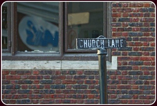 An old-fashioned Church Lane sign. Reflected in the window: the former Max's Art Supplies. (Photo/Lynn U. Miller)