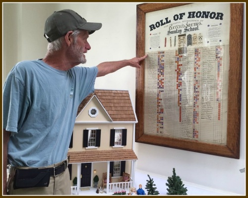 "Bob Custer points out some famous names -- Jennings, Sherwood, Wakeman, Rippe, Adams -- on a ""Wall of Honor."" Those on the list are cited for their  Sunday school attendance from 1909 to 1916."