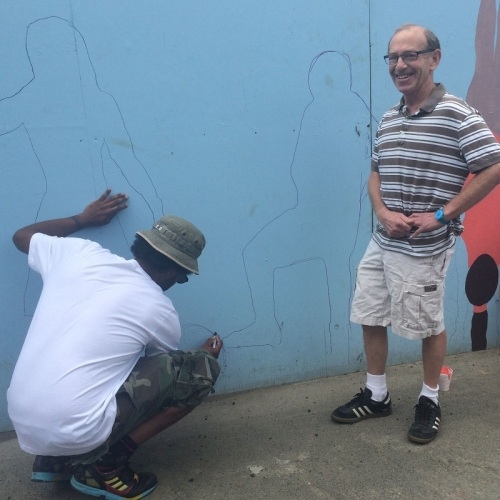 Jahmane -- the member of the Westport Artists Collective who painted the Minute Man at the east end of the wall -- traced yours truly. In the shot above, he's adding a soccer ball to the wall.