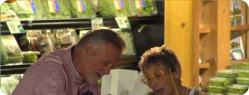 A Stew Leonard's shopper (left) is filmed by a hidden camera, patiently answering questions from an actress playing a chatty older shopper.