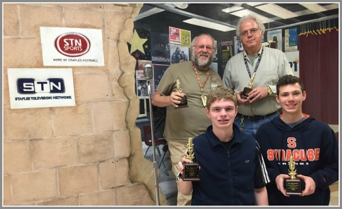 Mike Zito and Jim Honeycutt (rear) stand with WWPT-FM's Jack Caldwell and Cooper Boardman -- and some Drury Award trophies. Behind them is a mural -- painted by Staples art students -- on the wall outside the Media Lab.