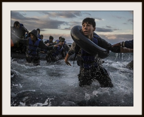"This photo by Tyler Hicks appears on the Pulitzer Prize website. The caption reads: ""After battling rough seas and high winds from Turkey, migrants arrive by rubber raft on a jagged shoreline of the Greek island of Lesbos. Fearing capsize or puncture, some panicked and jumped into the cold water in desperation to reach land. This young boy made it, unlike hundreds of others."" (Photo/Tyler Hicks, The New York Times - October 1, 2015)."