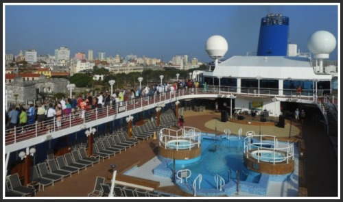 Adonia passengers line the deck as the ship enters Havana harbor.