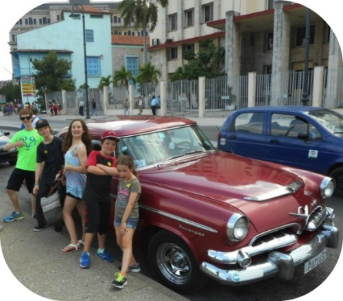 A classic Cuba photo: American kids from the Adonia surround a classic American car.