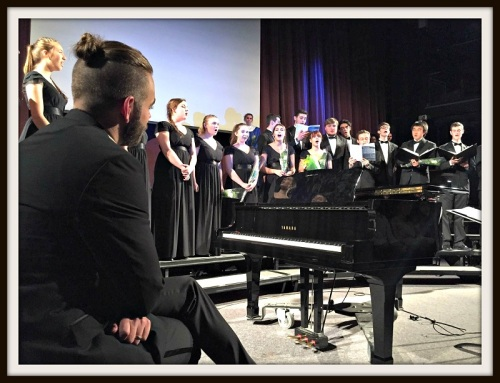 Luke Rosenberg (left) listens to his graduating seniors sing.