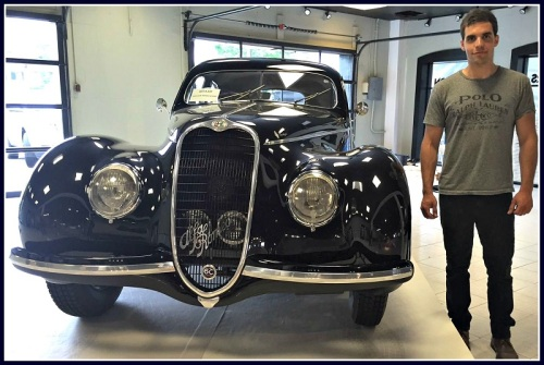 Dragone director of marketing Alex Dragone stands next to a one-of-a-kind 1939 Alfa Romeo -- perhaps the most expensive automobile in the auction.