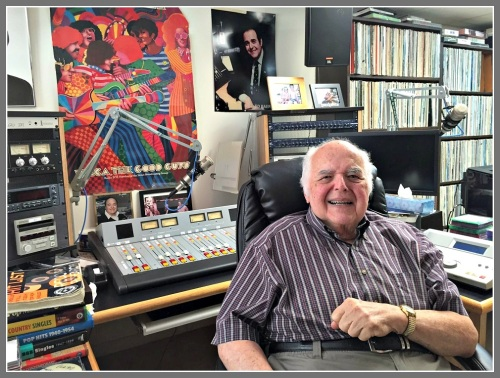 Ed Baer, relaxing in his home studio. A WMCA poster hangs on the wall. A few of his many records line the shelves.