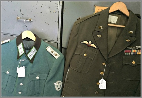Two of Ed's many uniforms hang on a file cabinet.