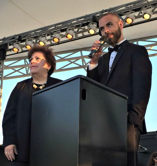 Orchestra leader Adele Valovich and choral director Luke Rosenberg address the audience.