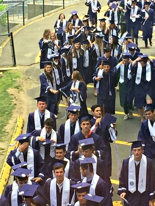 The class of 2016 congregates behind the filedhouse, before marching inside.