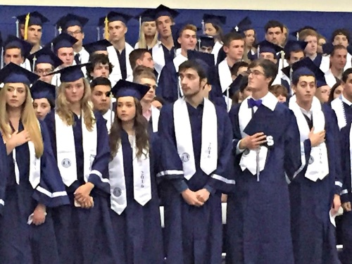 Graduates rise for the national anthem.