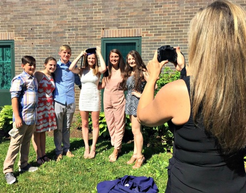 Nicole Donovan (right) photographs her family. Graduate Eliza (cap) is surrounded by her 5 siblings.