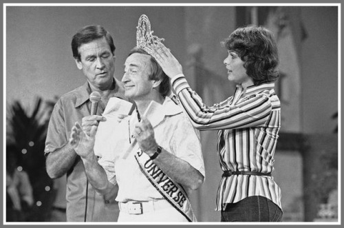 Gene Bayliss choreographed the Miss Universe pageant in 1977. Here he acts as a stand-in for the winner during rehearsal.. He's crowned by the reigning Miss Universe Rina Messinger, as host Bob Barker looks on.