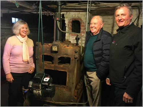 Sam Gault (right), president of Gault Energy & Home Solutions, delivered a new state-of-the-art Energy Kinetics System 2000 boiler to Willie and Anne Salmond.