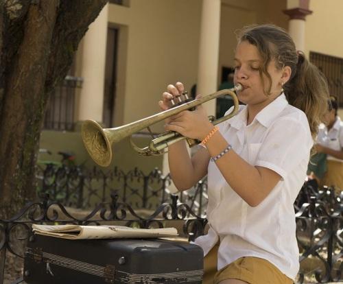 Girl practicing trumpet in high school courtyard. (Photo copyright June Eichbaum)